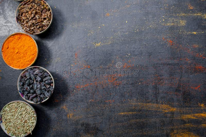 Spices. Colorful spices. Curry, Saffron, turmeric, cinnamon and otheron a dark concrete background. Pepper. Large collection of di. Fferent spices and herbs royalty free stock images