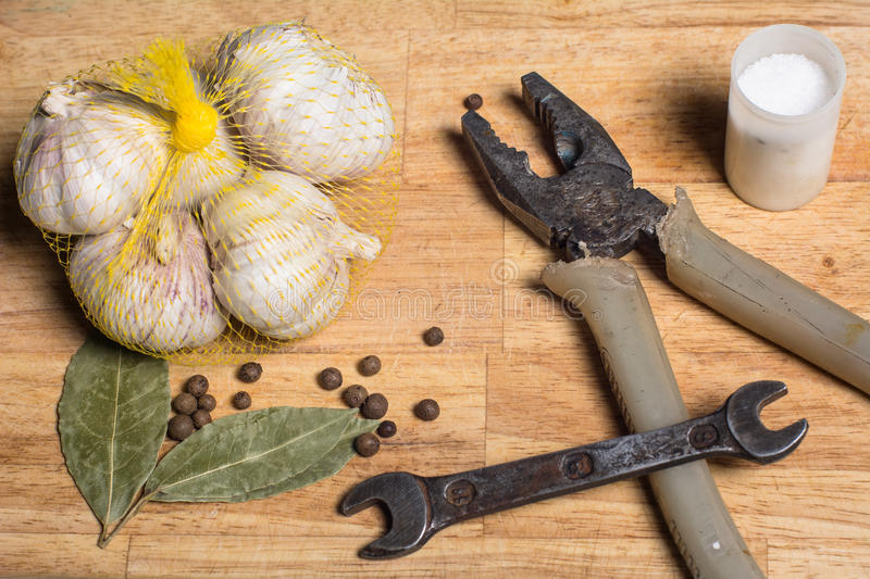 Spices on a cutting board and man`s tools. Spices on a cutting board and a man`s tools. Wrench and pliers on a kitchen board royalty free stock photos