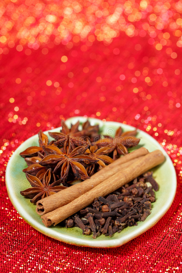 Spices - Gloves, Anis star, Cinnamon sticks. In plate on red glitter backdrop, Shallow DOF stock images