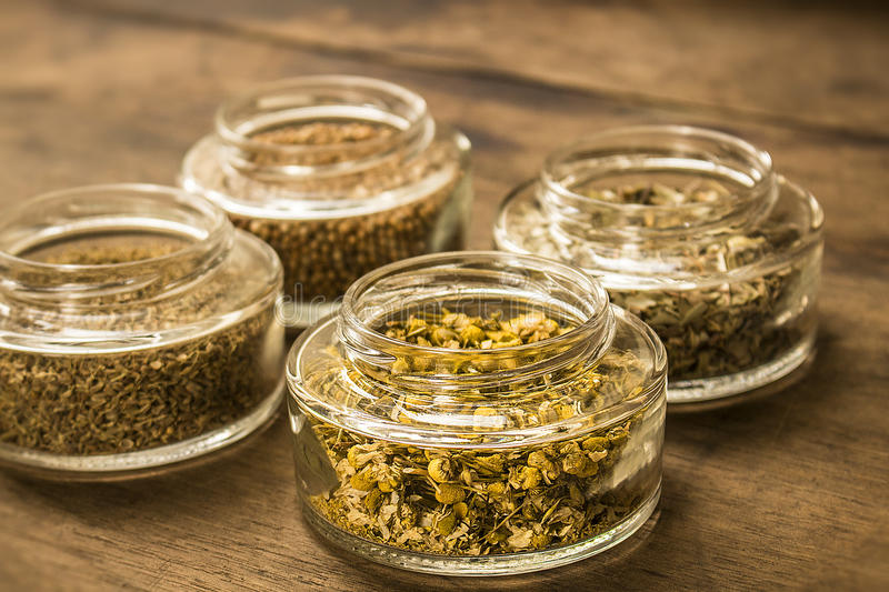 Spices and herbal tea ingredients on glass jars. Small glass jars full of spices and herbal tea ingredients (coriander seeds, cloves, dry chamomile flowers and stock photo