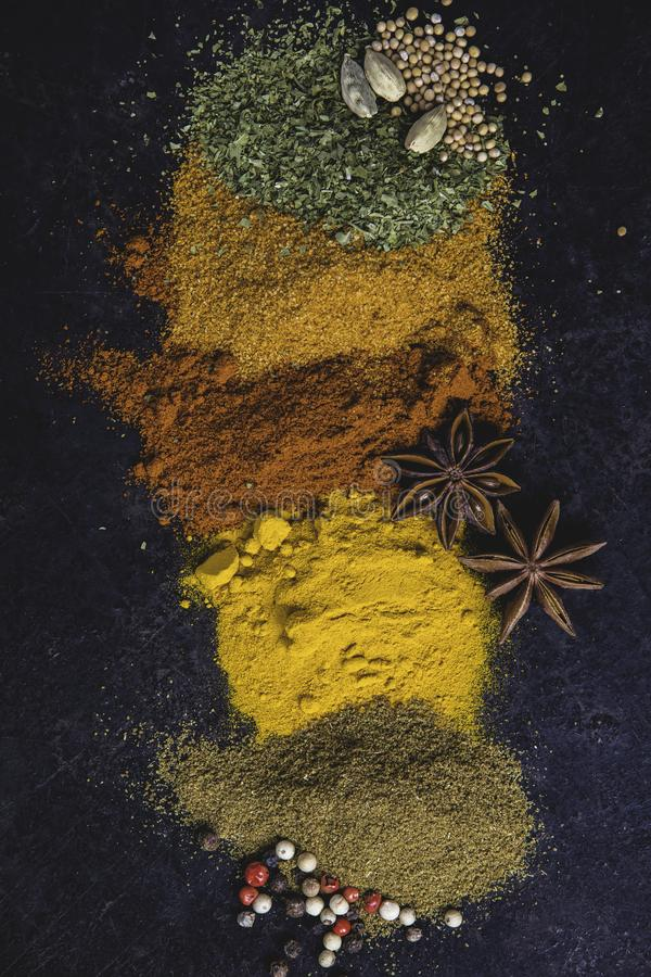 Spices and herbs on a dark background. Paprika, parsley, cumin, curcuma, pepper, anice and mustard seeds. Cooking and healthy eating concept stock photo