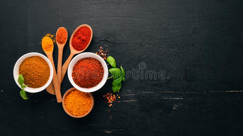 Spices and herbs on a wooden board. Pepper, salt, paprika, basil, turmeric. On a black wooden chalkboard. Top view. Free copy space royalty free stock photos