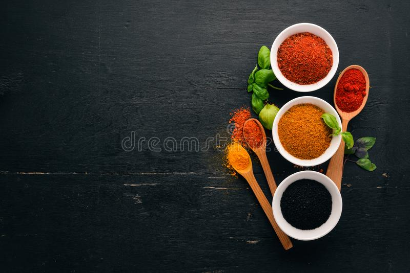 Spices and herbs on a wooden board. Pepper, salt, paprika, basil, turmeric. On a black wooden chalkboard. Top view. Free copy space stock images