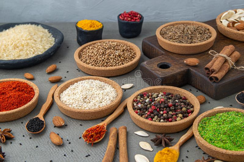 Spices lie in bowls and wooden spoons on a gray background , top view, soft focus. royalty free stock photos
