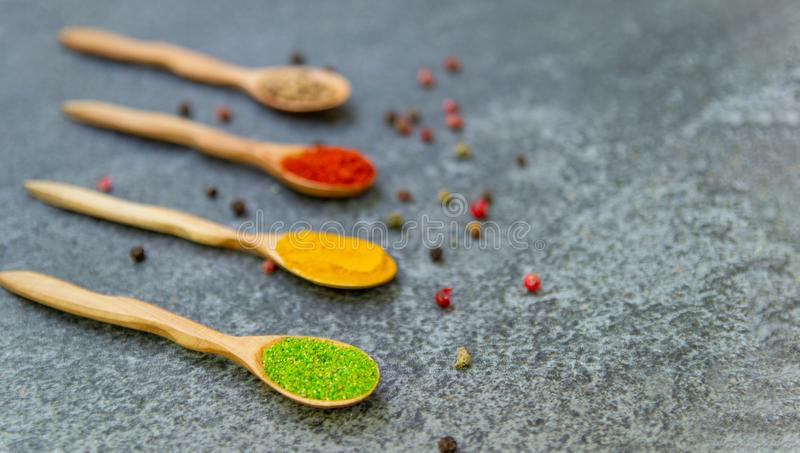 Spices lie in wooden spoons on a black background, top view, soft focus. stock images