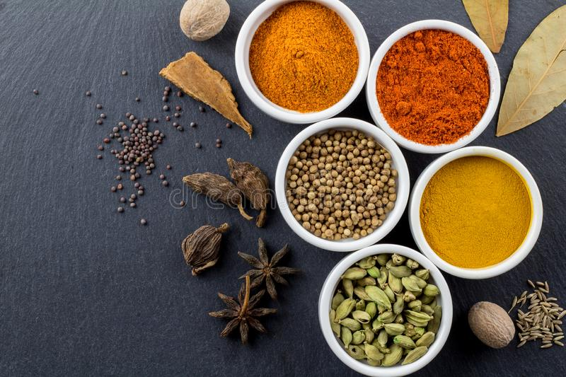 Spices in little white bowls on black slate background - Indian spice - top view photo stock photos