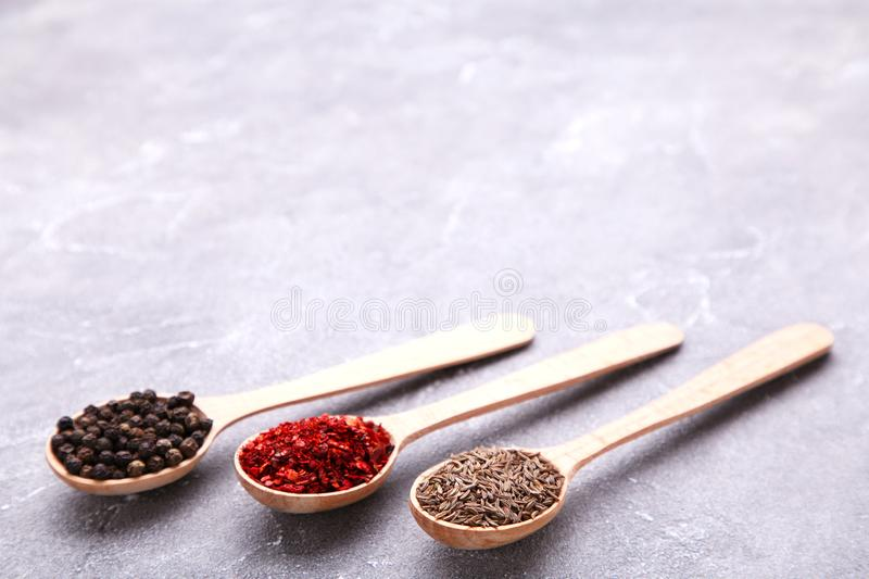 Spices mix on wooden spoons on a grey background. Top view stock photography