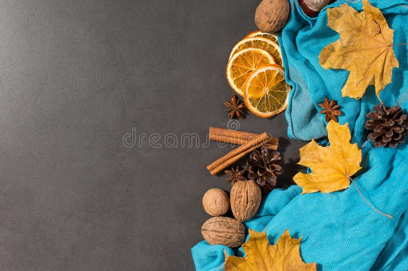 Spices, a scarf, nuts, dry leaves and oranges on a stone table. Autumn mood, a method to keep warm in the cold, copy space. Spices, a scarf, nuts, dry leaves and stock photography