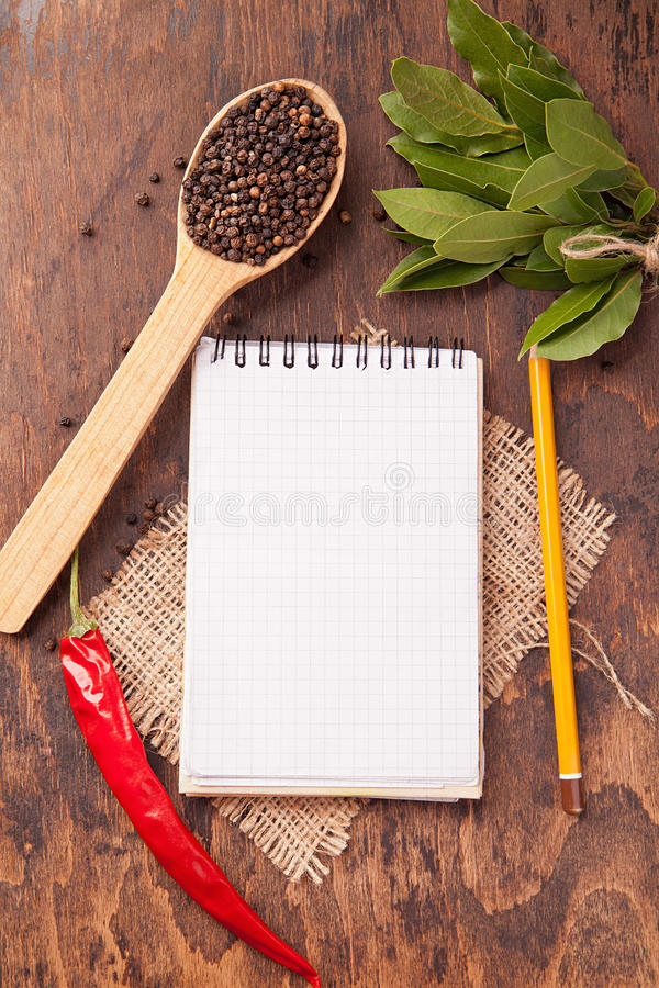 Spices in spoons, notebook on wood background. Red chili pepper, garlic, bay leaf, spices in spoons, old notebook on oak wood texture background. Spices stock image