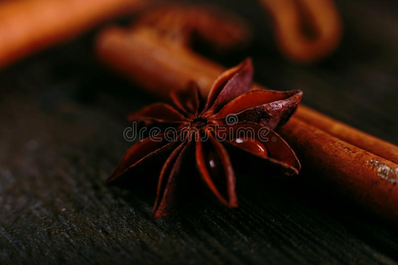 Spices sticks cinnamon and star anise on the old table. Rustic dark background, aroma close-up, macro stock photo