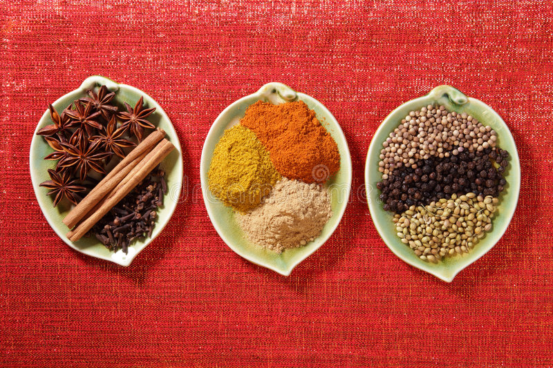 Spices in three leaf shape plates on glitter red stock photography