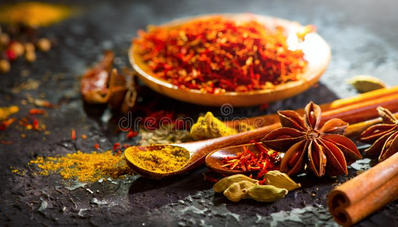 Spices. Various Indian spices on black stone table. Spice and herbs on slate background. Cooking ingredients stock image