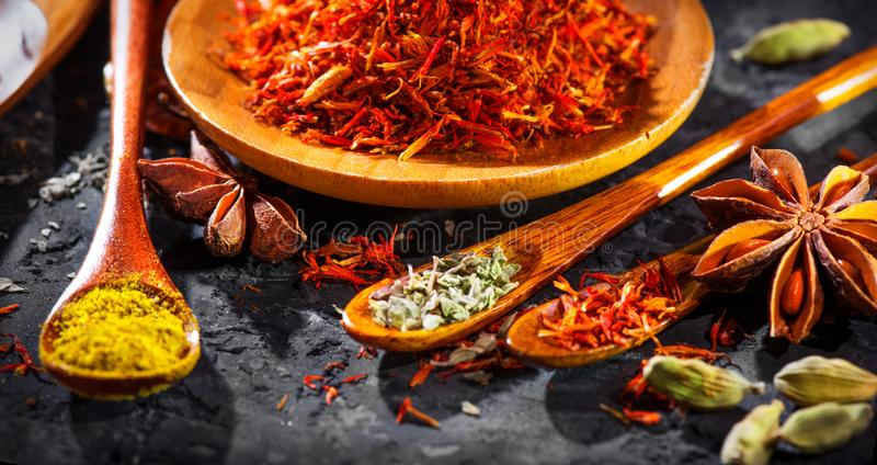Spices. Various Indian Spices on black stone table. Spice and herbs on slate background. Assortment of Seasonings, condiments. Cooking ingredients, flavor stock image