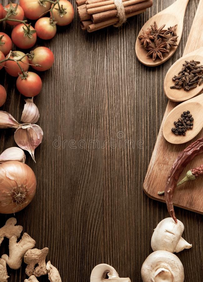 Spices and vegetables in anticipation of cooking on a wooden table.  stock photo