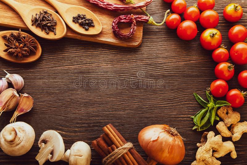 Spices and vegetables in anticipation of cooking. On a wooden table royalty free stock photo