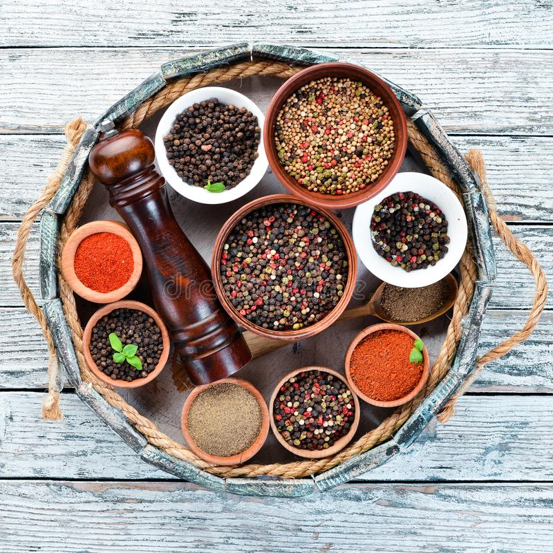 Spices in a wooden box. Colored pepper, sea salt, ground pepper, chili pepper. Top view stock images