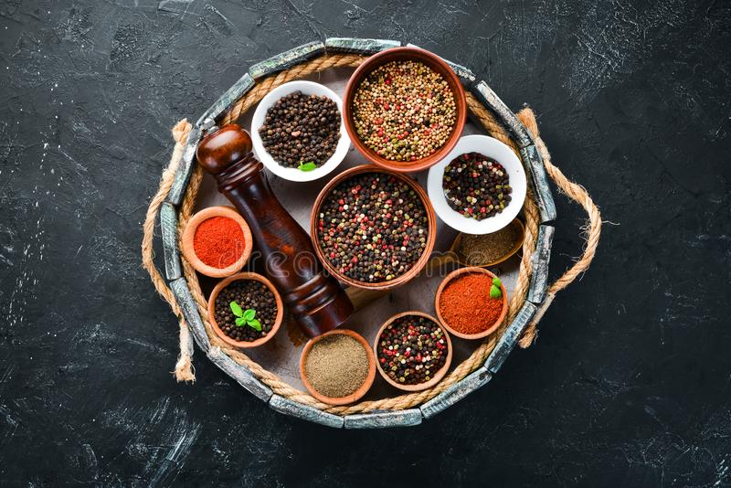 Spices in a wooden box. Colored pepper, sea salt, ground pepper, chili pepper. Top view royalty free stock photography