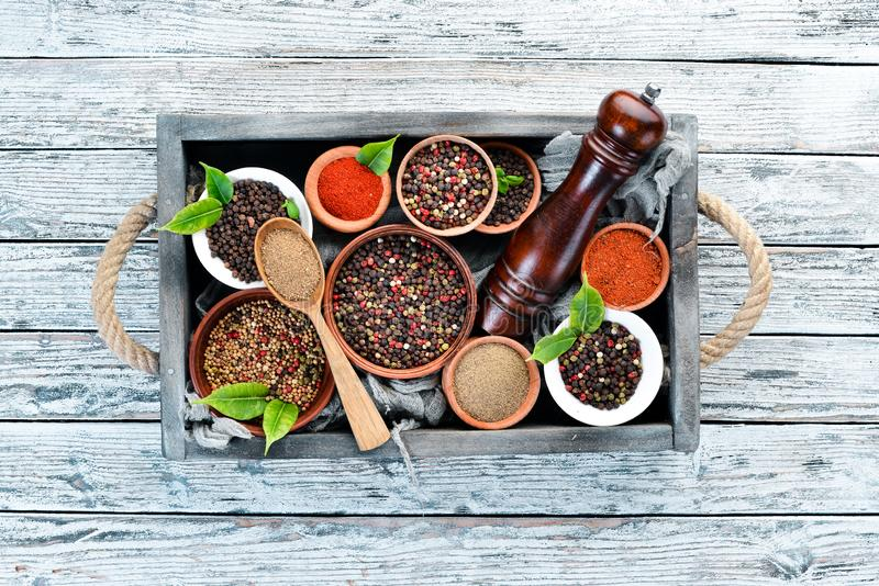 Spices in a wooden box. Colored pepper, sea salt, ground pepper, chili pepper. Top view stock photography