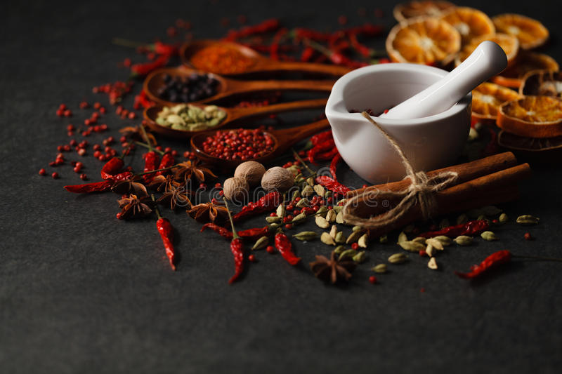 Spices in wooden spoon on dark stone surface royalty free stock image
