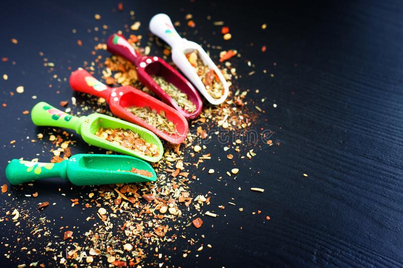 Spices and wooden spoons on black stock images