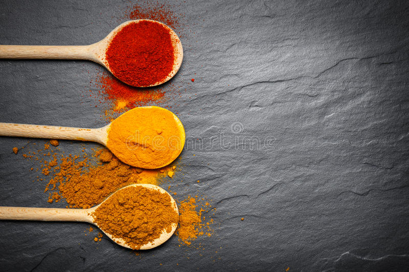 Spices in wooden spoons royalty free stock image