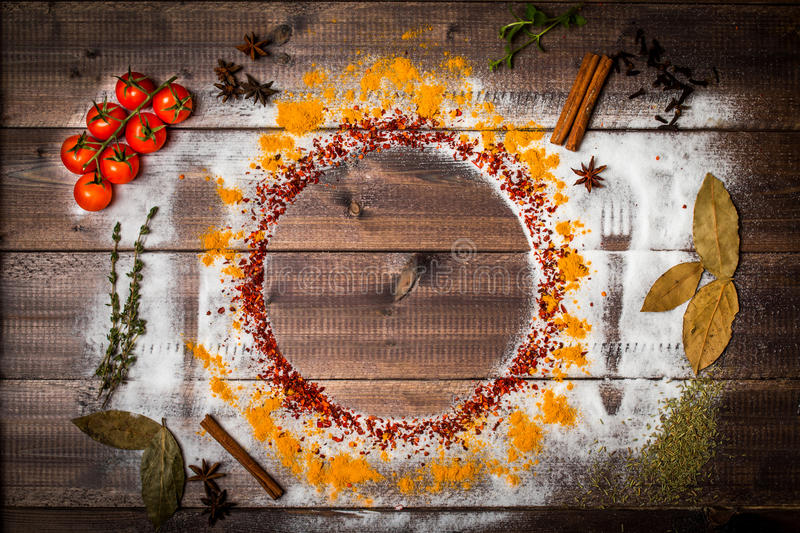 Spices on wooden table with cutlery silhouette. Colorful spices on wooden table with cutlery silhouette, top view royalty free stock images