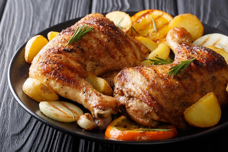 Spicy bbq chicken legs with grilled oranges, onions, garlic and royalty free stock photo