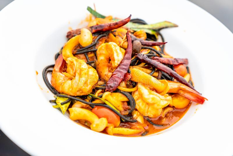 Spicy black spaghetti with shrimps (tom yum kung. ) - fusion food style stock image