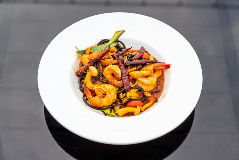 Spicy black spaghetti with shrimps (tom yum kung. ) - fusion food style royalty free stock photography