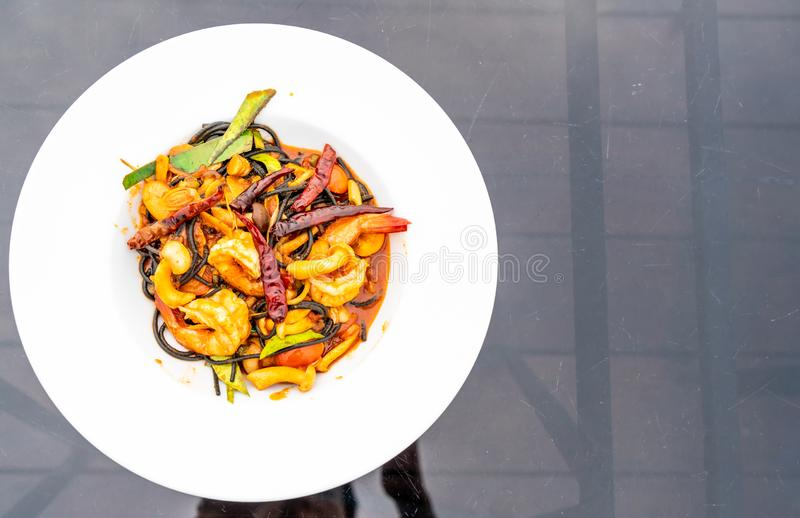 Spicy black spaghetti with shrimps (tom yum kung. ) - fusion food style royalty free stock photos