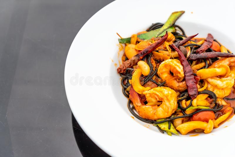 Spicy black spaghetti with shrimps (tom yum kung. ) - fusion food style stock images