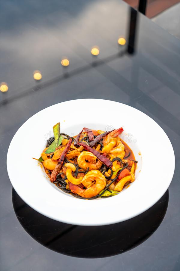 Spicy black spaghetti with shrimps (tom yum kung. ) - fusion food style stock photo
