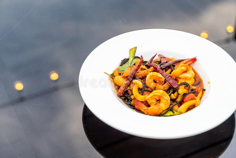 Spicy black spaghetti with shrimps (tom yum kung. ) - fusion food style stock photos