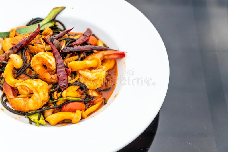 Spicy black spaghetti with shrimps (tom yum kung. ) - fusion food style stock photography