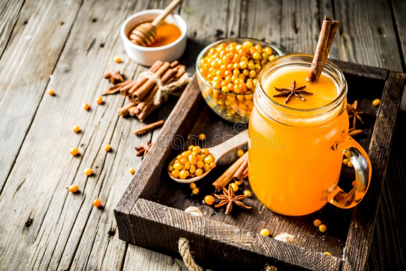 Spicy buckthorn hippophae tea. Spicy buckthorn hippophae drink - tea, juice or smoothie, with cinnamon and anise, rustic wooden background copy space royalty free stock photography