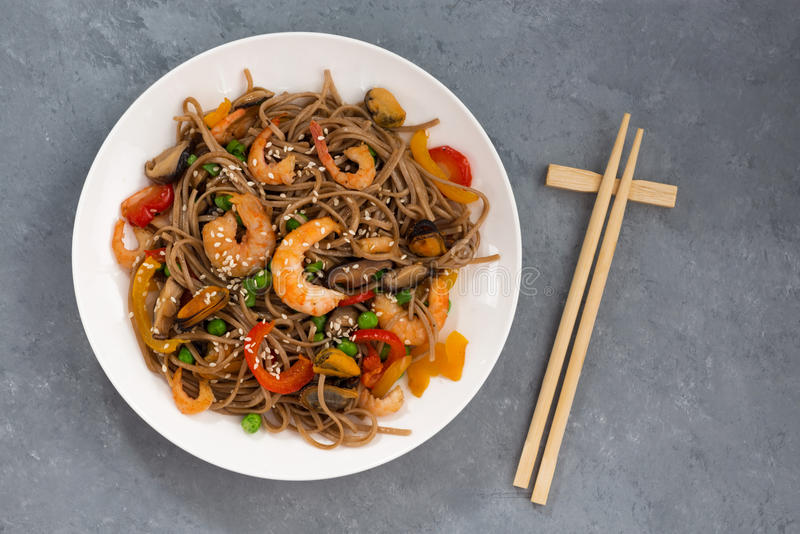 Spicy buckwheat noodles with seafood and vegetables, top view stock images