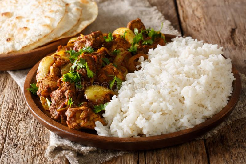 Spicy Chicken do pyaza curry which has double the amount of onions with garnish of rice close-up on a plate. Horizontal. Spicy Chicken do pyaza curry which has royalty free stock photo