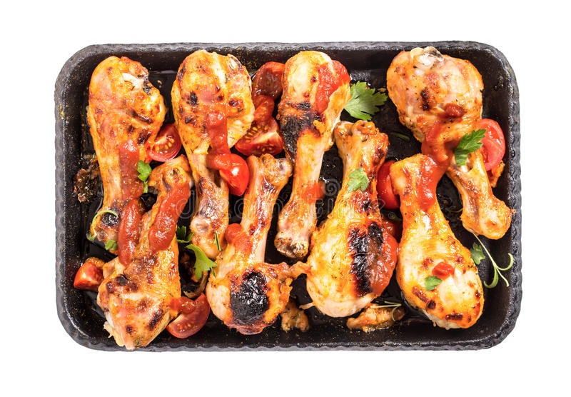 Spicy chicken drumsticks on serving pan isolated. Spicy chicken drumsticks on serving pan. Top view. Isolated stock images
