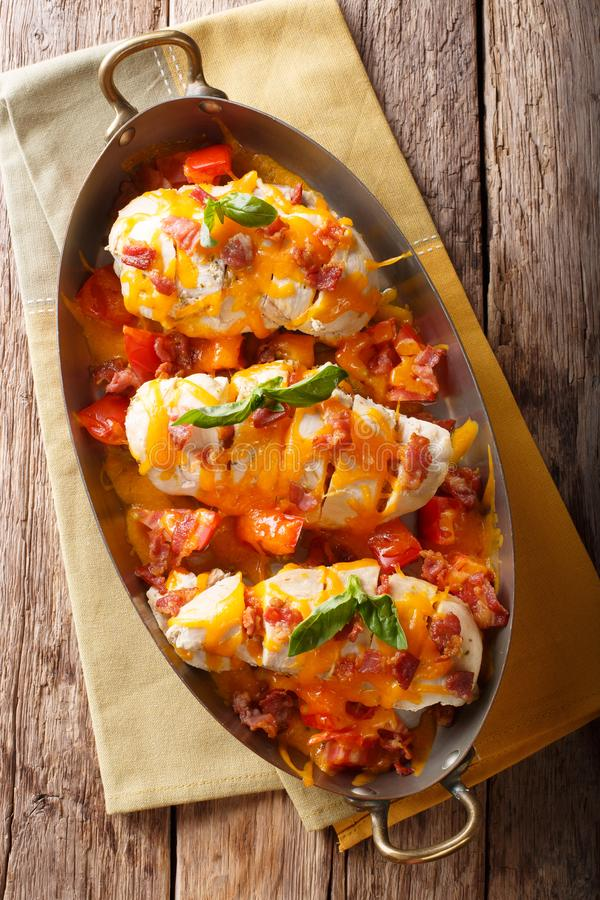 Spicy chicken fillet baked with bacon, tomatoes and cheddar cheese close-up in a pan. Vertical top view royalty free stock images
