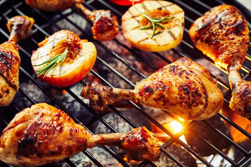 Spicy chicken legs sizzling over a hot barbecue. With halved fresh apricots or nectarines seasoned with rosemary in a close up view royalty free stock photography