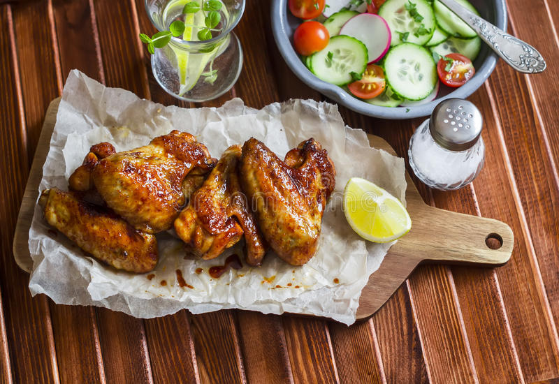 Spicy chicken wings and fresh vegetable salad stock photos