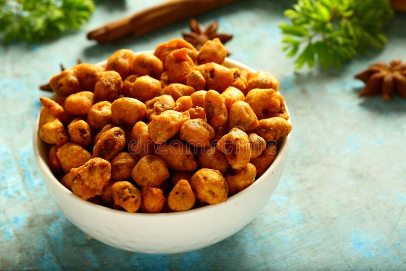 Spicy coated peanuts in white bowl stock photos