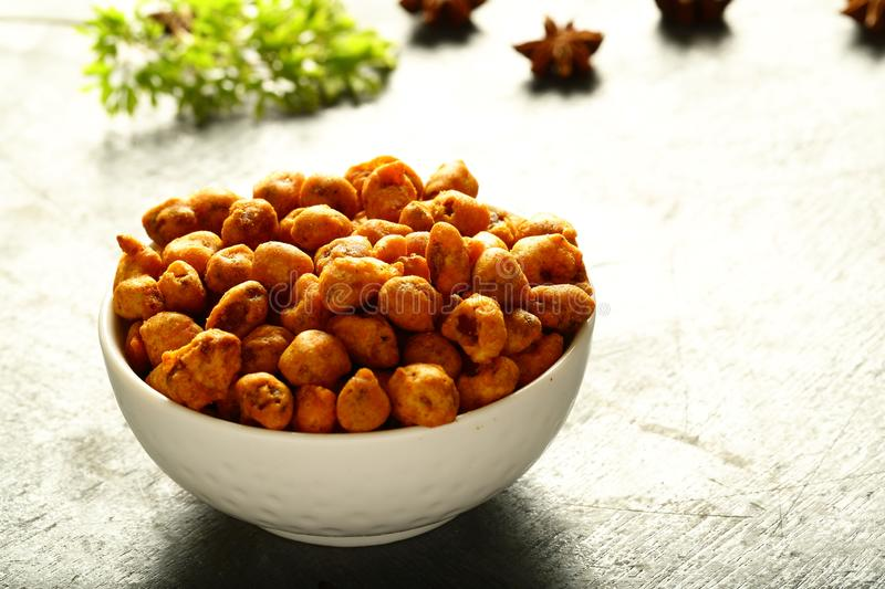 Spicy coated peanuts in white bowl stock photography