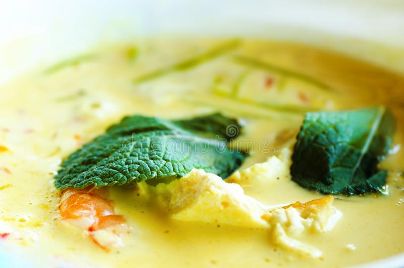 Spicy coconut milk cream soup curry with chiken, tiger prawns, long soy noodles, bean sprouts, lime, chilli pepper and royalty free stock photo