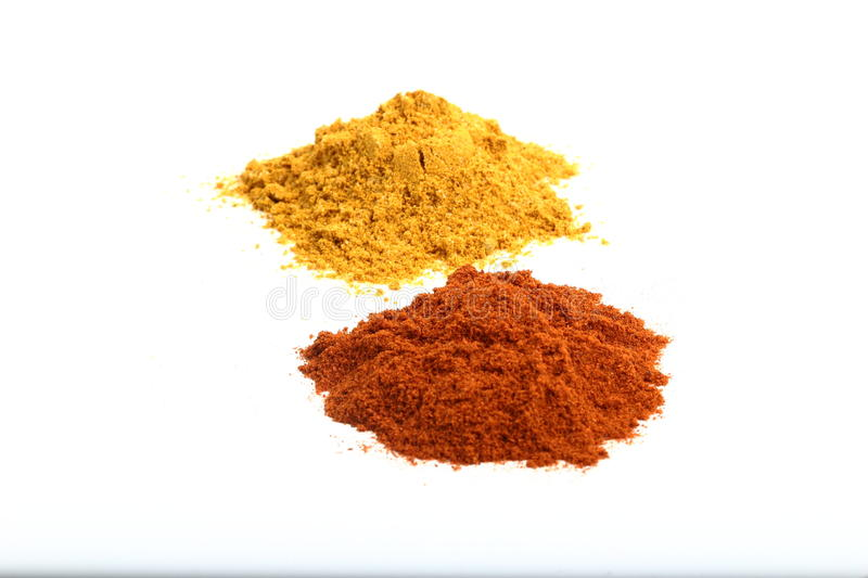 Spicy condiments. Heaps of turmeric and red paprika powder on a white background stock photo