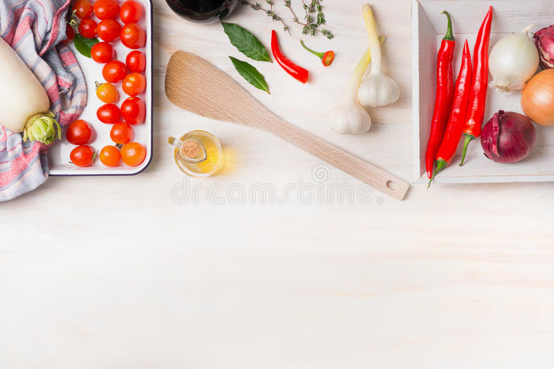 Spicy cooking. Various spices, olive oil, chili, onion, garlic and Bay leaves with cooking spoon on white wooden background, top v. Iew, border. Healthy food royalty free stock images