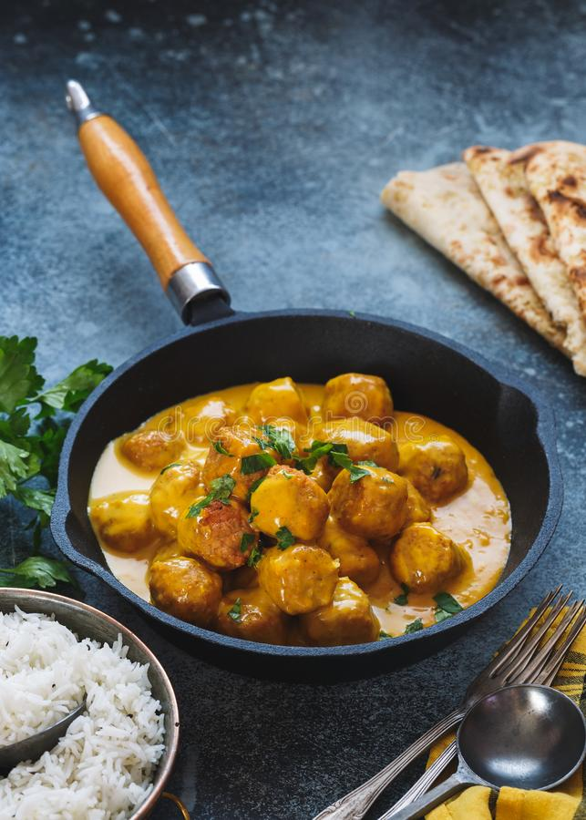 Spicy curry dish with meatballs served with pilau rice and naan bread royalty free stock photo