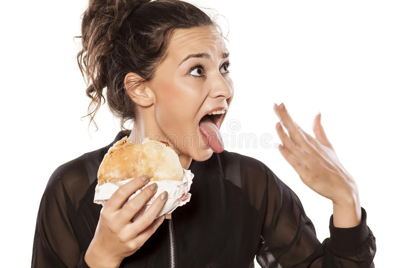 Spicy food. Young woman with spicy sandwich and burning tongue stock image