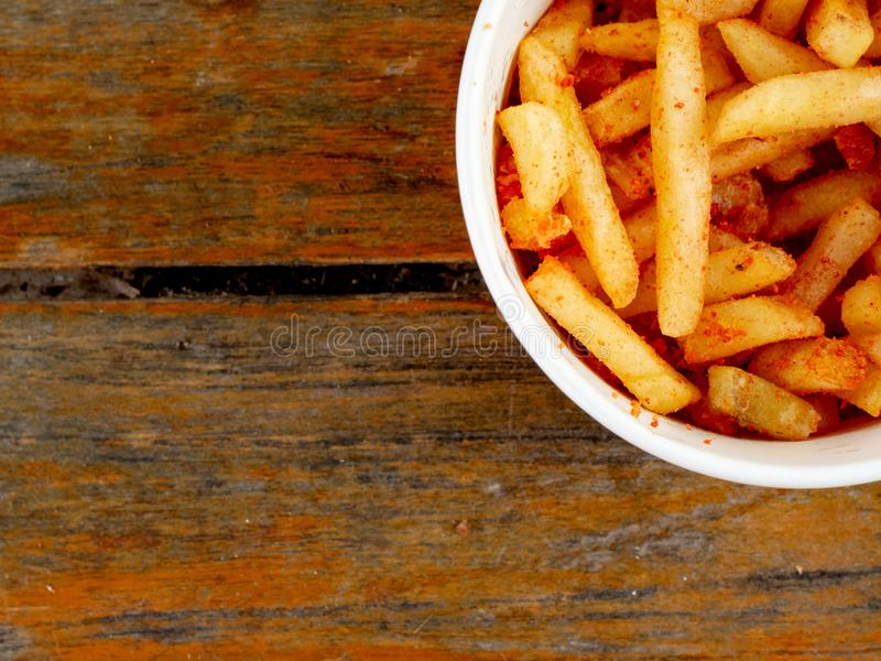 Spicy french fries. A spicy french fries on brown wood table stock photography