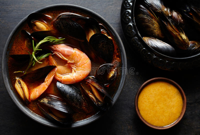 Spicy french soup bouillabaisse with seafood, prawns, mussels. Traditional in France, Spain. Dark rustic style. royalty free stock image